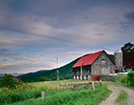 Wooden Barn with Red Roof under Cloudy Skies