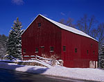 Newly-painted Old Red Barn with Fence and Stonewall after Snowfall
