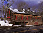 Cedar-shingled Barn with Stone Foundation in Winter