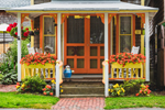"""Porch of Orange and Yellow Gingerbread House """"Oops"""", Martha's Vineyard Camp Meeting Association, National Register of HIstoric Places, Oak Bluffs, MA"""