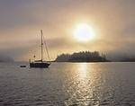 Sunrise through Fog with Sloop at Anchor