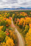 Aerial View of Unpaved Country Road through Forest with Brilliant Fall Foliage, Moosehead Lake and Mountains in Distance, off Moosehead Lake Scenic Byway, Lily Bay Township, ME