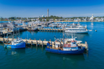 Commercial Fishing Boats at Dock in Provincetown Harbor, with Pilgrim Monument in Background, Cape Cod, Provincetown, MA