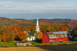 Early Evening Light Shines on Cornfield, Red Barns, and The Congregational Church of Peacham in Autumn, Northeast Kingdom, Peacham, VT