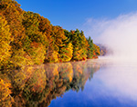 Early Morning Fog Rising over Fort Pond with Fall Foliage and Reflections along Shoreline