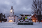 Dusk Descends upon Gazebo with Garlands and Holiday Lights in Winter, Historic Hancock Meeting House and Congregational Church in Background, Hancock, NH