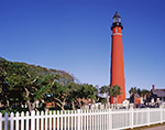 Ponce de Leon Inlet Lighthouse with White Picket Fence under Bright Blue Sky