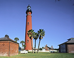 Bright Blue Sky over Ponce de Leon Inlet Lighthouse with Three Palm Trees