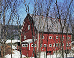 Big Red Barn with White Trim seen through Trees in Late Winter