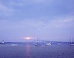 Sun Peeking through Storm Clouds at Sunset over Boats, Goat Island Lighthouse and Newport Bridge, Newport Harbor, Newport, RI