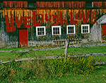 """Live, Laugh, Love"" on Side of Wooden Barn with Red Door, White Window Trim and Split-rail Fence in Front, near Village of Quechee, Hartford, VT"