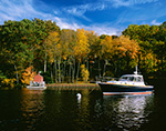 "Power Cruiser ""Syncopation"" and Little Red Boat House in Hamburg Cove in Fall, Eightmile River, Popular Boating Spot on the Connecticut River,  Lyme, CT"