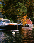 """Power Cruiser """"Syncopation"""" and Little Red Boat House in Hamburg Cove in Fall, Eightmile River, Popular Boating Spot on the Connecticut River,  Lyme, CT"""
