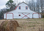 White Barn with Red Trim and Haybales in Foreground. Haralson County, GA