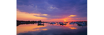 Sunset with Bright Sun between Dark Clouds and Water over Boats in Polpis Harbor, Nantucket, MA