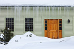 Close-up of Colonial-style Home in Winter with Deep Snow and Icicles, Royalston, MA