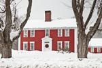 Sugar Maple Trees and Red and White Colonial Home with Holiday Wreath during Snowstorm, Fitzwilliam, NH