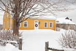 Yellow Colonial-style Home with Holiday Wreath after Snowstorm, Rindge, NH