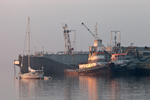 Sailboat Dwarfed by Tugboats and Large Barge in Early Morning Light, Rockland Harbor, Rockland, ME