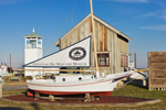 """Mini Skipjack """"Spat"""" with Point Lookout Tower in Boat Yard at Chesapeake Bay Maritime Museum, St Michaels, MD"""