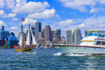 """Schooner """"Fame"""" under Full Sail in Boston Harbor with Power Boat Crossing Its Bow, Boston Skyline and Waterfront in Background, Boston, MA"""