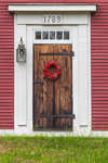 Close Up View of Old Wooden Door with Red Berry Wreath on Old Colonial House, Cape Cod, Sandwich, MA