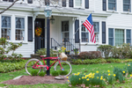 Old Bicycle, Daffodils, and American Flag in Spring at Colonial-style Home, Athol, MA