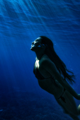 Young woman swims to the surface of Honaunau Bay, Big Island, Hawaii