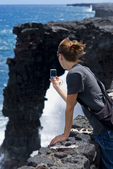 Visitor shoots cellphone picture of Holei Sea Arch, Hawaii Volcanoes National Park, Big Island, Hawaii