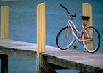 Pink bicycle on wooden pier. 