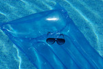 Sunglasses on blue float in pool.