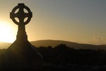 Celtic cross at sunset in cemetery, Ireland.