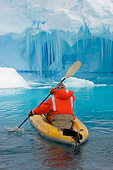 Antarctica, near Peterman Island, kayaker paddles near blue ice berg, near Peterman Island, Antarctica