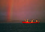 Ship Yamato steaming through Beagle Channel, with storm light and rainbow