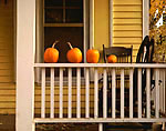 Pumpkins arranged along the porch rail of a yellow house near Nashville, Brown County, Indiana, USA, October, M547.