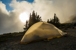 Backpacking tent at Camp Kiser with the sun setting behind, along the Ptarmigan Ridge Trail, Mount Baker-Snoqualmie National Forest in the North Cascades, Washington State, USA