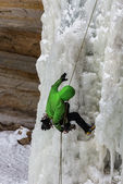 Ice climber rappelling down a frozen waterfall, viewed along the Munising Ski Trail, which is operated by the National Park Service in the Sand Point area of Pictured Rocks National Lakeshore in the Upper Peninsula of Michigan, USA [Note: No model release; available for editorial licensing only]