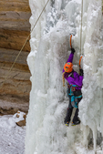 Woman ice climber using ice tools to ascend a frozen waterfall, viewed along the Munising Ski Trail, which is operated by the National Park Service in the Sand Point area of Pictured Rocks National Lakeshore in the Upper Peninsula of Michigan, USA [Note: No model release; available for editorial licensing only]