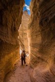 Karen Rentz hiking through the narrow slot canyon along the Slot Canyon Trail at Kasha-Katuwe Tent Rocks National Monument in New Mexico, USA