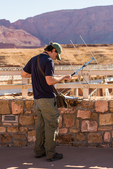 A staff member of The Peregrine Fund using a radio antenna to track the movements of California Condors, Gymnogyps californianus, from the Historic Navajo Bridge over Marble Canyon and the Colorado River, at the border ofGlen Canyon National Recreation Area and dthe Navajo Nation, Arizona, USA [No model release; available for editorial licensing only]