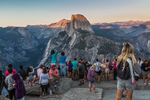 Visitors at Glacier Point, viewing the sunset over Half Dome and Yosemite Valley in Yosemite National Park, California, USA [Note: no model releases; available for editorial licensing only]
