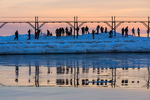 Photographers and sightseers lined up on the South Pier to see sunset on the Grand Haven Lighthouse, at the mouth of the Grand River where it enters Lake Michigan, Grand Haven, Michigan, USA [No model releases; available for editorial licensing only]