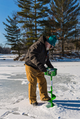 Drilling a hole in the ice for ice fishing with a battery-powered ice auger at Lake of the Clouds, Canadian Lakes, Stanwood, Michigan, USA [No model release; available for editorial licensing only]