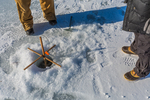 Setting a tip-up over a hole in the ice while ice fishing at Lake of the Clouds, Canadian Lakes, Stanwood, Michigan, USA