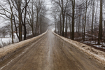 Icy country road melting out during a January thaw near Stanwood, Michigan, USA