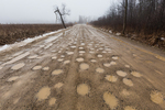 Sand road with potholes during a January thaw in central Michigan, USA