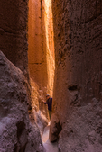 Karen Rentz exploring one of the slot canyons in the siltstone cliffs that locals refer to as caves, Cathedral Gorge State Park, Nevada, USA