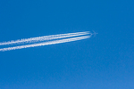 Jet leaving contrails high above  Lassen National Forest, California, USA