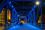 Group walking dogs at night on the Blue Bridge over the Grand River in Grand Rapids, Michigan, USA