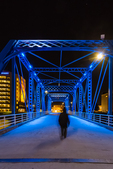 Woman walking alone at night across the Blue Bridge over the Grand River in Grand Rapids, Michigan, USA